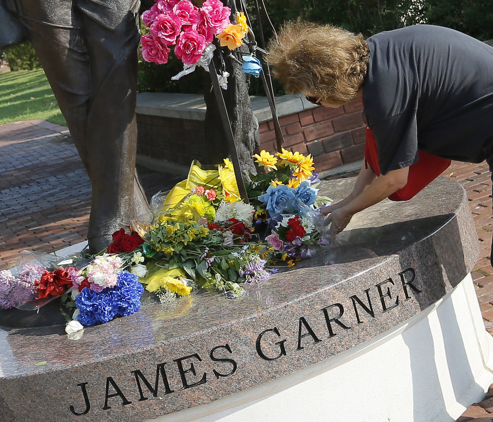 Photo - Katrina Prince, a fan of James Garner and Norman resident, places flowers on the statue of James Garner on Main St. in downtown Norman, Okla., Sunday, July 20, 2014. Garner died Saturday at age 86. Photo by Nate Billings, The Oklahoman