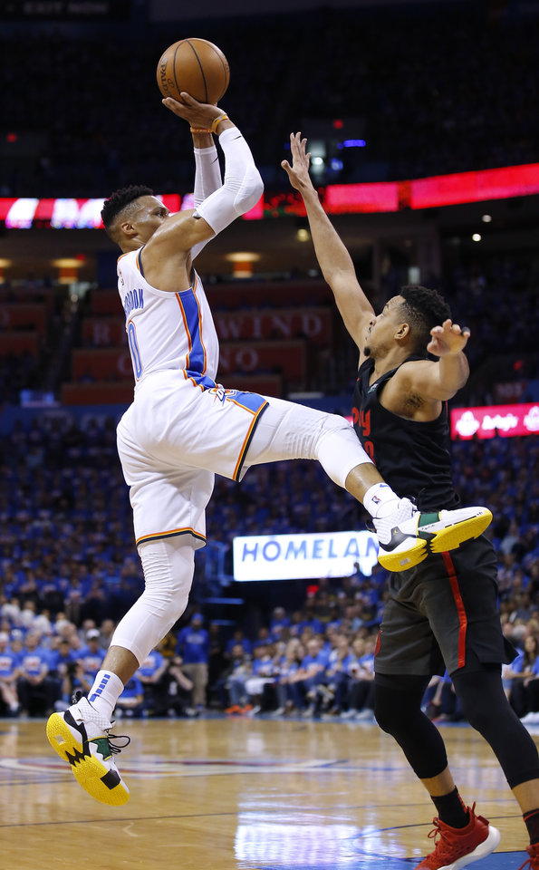 Photo - Oklahoma City's Russell Westbrook (0) shoots as Portland's CJ McCollum (3) defends during Game 4 in the first round of the NBA playoffs between the Portland Trail Blazers and the Oklahoma City Thunder at Chesapeake Energy Arena in Oklahoma City, Sunday, April 21, 2019.  Photo by Sarah Phipps, The Oklahoman