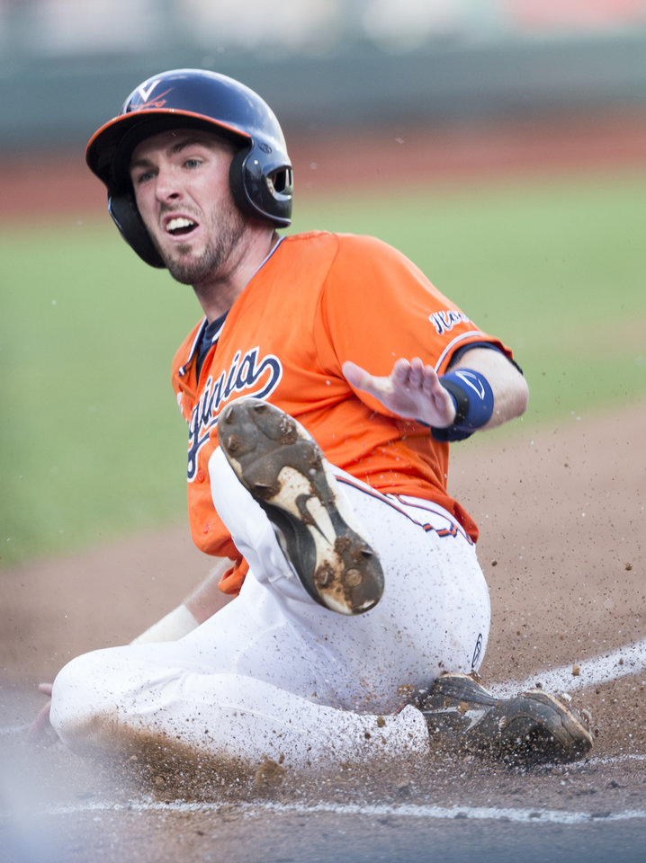 Photo - Virginia's Branden Cogswell scores against TCU on a throwing error in the first inning of an NCAA baseball College World Series game in Omaha, Neb., Tuesday, June 17, 2014. (AP Photo/Nati Harnik)