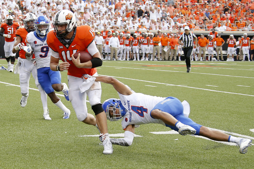 Photo -  Oklahoma State's Taylor Cornelius (14) fights off Boise State's DeAndre Pierce (4) en route to 41-yard day rushing. [Photo by Bryan Terry, The Oklahoman]