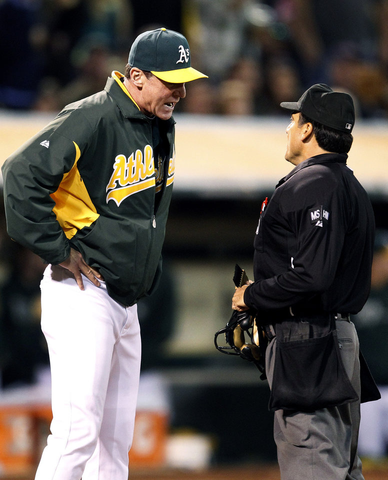 Photo -   Oakland Athletics manager Bob Melvin, left, argues a call with home plate umpire Phil Cuzzi in the sixth inning against the Boston Red Sox in a baseball game Saturday, Sept. 1, 2012 in Oakland, Calif. (AP Photo/Tony Avelar)