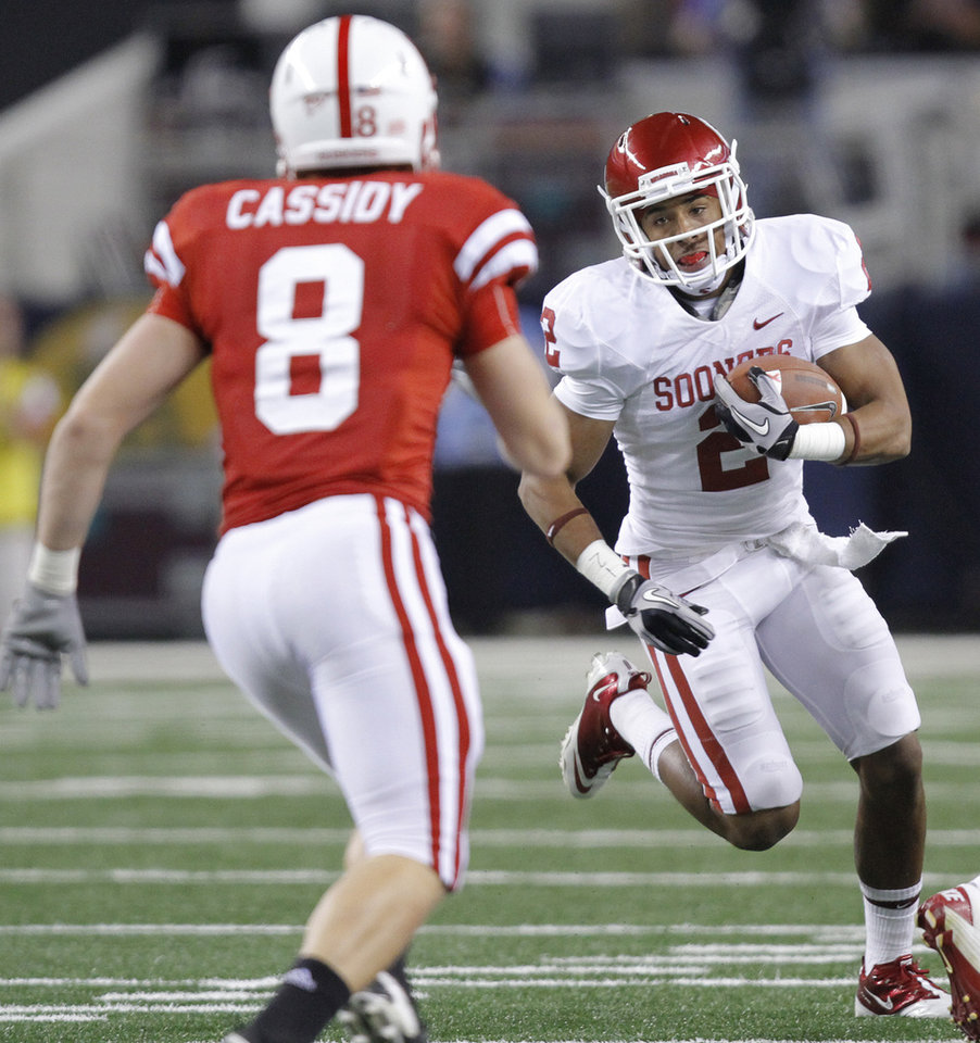 Photo - Oklahoma's Trey Fanks (2) looks for running room past Nebraska's Austin Cassidy (8) during the Big 12 football championship game between the University of Oklahoma Sooners (OU) and the University of Nebraska Cornhuskers (NU) at Cowboys Stadium on Saturday, Dec. 4, 2010, in Arlington, Texas.  Photo by Chris Landsberger, The Oklahoman