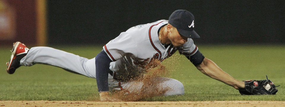 Photo - Atlanta Braves shortstop Andrelton Simmons stops a grounder by Chicago White Sox's Gordon Beckham before throwing him out at first base during the seventh inning of a baseball game in Chicago, Friday, July 19, 2013. (AP Photo/Paul Beaty)