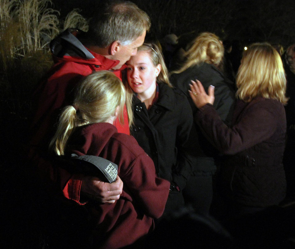 Photo - A man hugs his young daughters as they attend a vigil at Saint Rose of Lima church at Saint Rose of Lima church, Friday, Dec. 14, 2012 in Newtown, Conn. A man killed his mother at home and then opened fire Friday inside the elementary school where she taught, massacring 26 people, including 20 children, as youngsters cowered in fear to the sound of gunshots echoing through the building and screams coming over the intercom. (AP Photo/The Journal News, Frank Becerra Jr.)  NYC OUT, NO SALES, ONLINE OUT, TV OUT, NEWSDAY INTERNET OUT; MAGS OUT