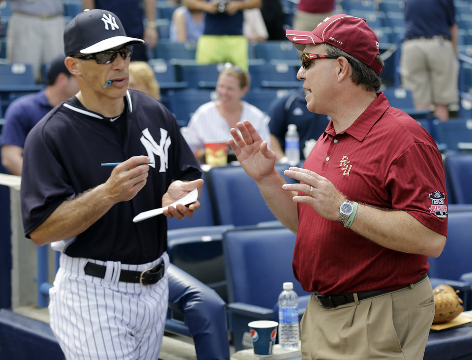 Photo - Florida State head football coach Jim Fisher, right, talks to New York Yankees manager Joe Girardi before a spring training exhibition game Tuesday, Feb. 25, 2014, in Tampa, Fla. Fisher threw out the ceremonial first pitch before the exhibition game. (AP Photo/Chris O'Meara)