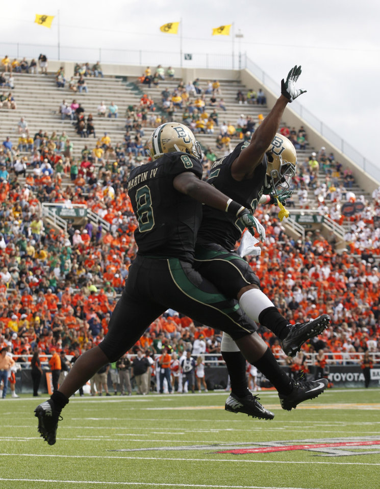 Baylor running back Lache Seastrunk (25) celebrates his touchdown with teammate  Glasco Martin (8) during the first half of an NCAA college football game against Oklahoma State, Saturday, Dec. 1, 2012, in Waco, Texas. Baylor won 41-34. (AP Photo/LM Otero)