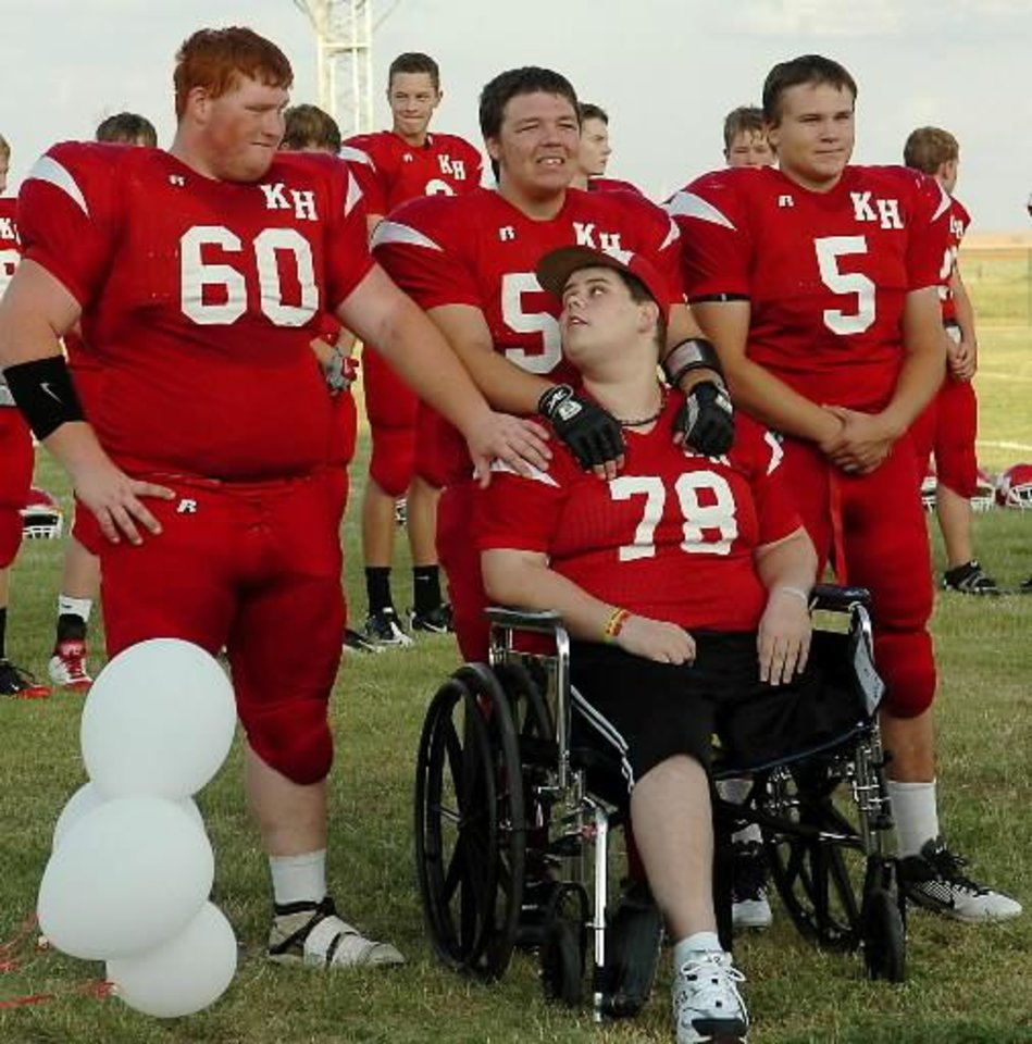 Photo - Bryce Gannon (front, seated) visits with Jeremy Maxwell, Alex Hicks and Tanner Rogers (from left) prior to the Kremlin-Hillsdale football homecoming celebration at Bronc Field, Friday, Sept. 9, 2011. Gannon, who was critically injured in a grain auger accident Aug. 4 at the Kremlin Grain Company, was named homecoming king during the festivities. (Photo by BONNIE VCULEK, ENID NEWS & EAGLE)