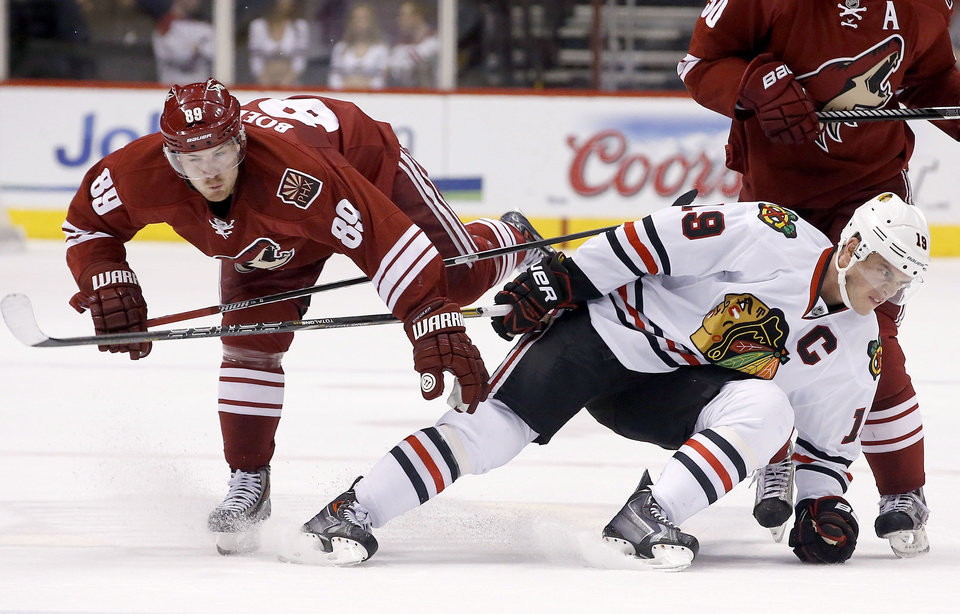 Photo - Chicago Blackhawks' Jonathan Toews, right, gets tangled up with Phoenix Coyotes' Mikkel Boedker (89), of Denmark, during the first period in an NHL hockey game Friday Feb. 7, 2014, in Glendale, Ariz.  The Coyotes defeated the Blackhawks 2-0. (AP Photo/Ross D. Franklin)