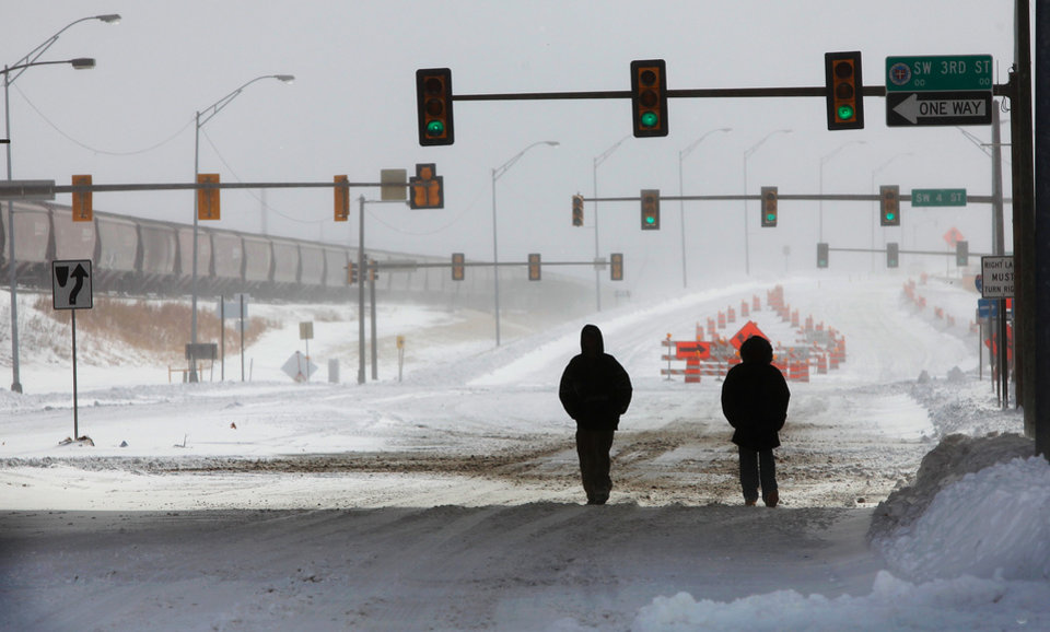 Photo - Two people walk north on Shields Boulevard into the downtown area as the sun emerges briefly from heavy clouds. A  severe winter storm created whiteout conditions and caused snow drifts that made problems for the few motorists who ventured out Tuesday afternoon, Feb. 1, 2011.   Photo by Jim Beckel, The Oklahoman