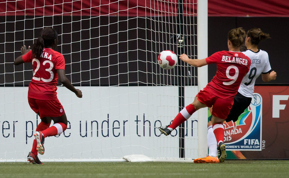 Photo - Germany's Lena Lotzen, right, scores a goal as Canada's Sura Yekka, left, and Josee Belanger defend during the first half of an international women's soccer game in Vancouver, British Columbia on Wednesday, June 18, 2014.  (AP Photo/The Canadian Press, Darryl Dyck)