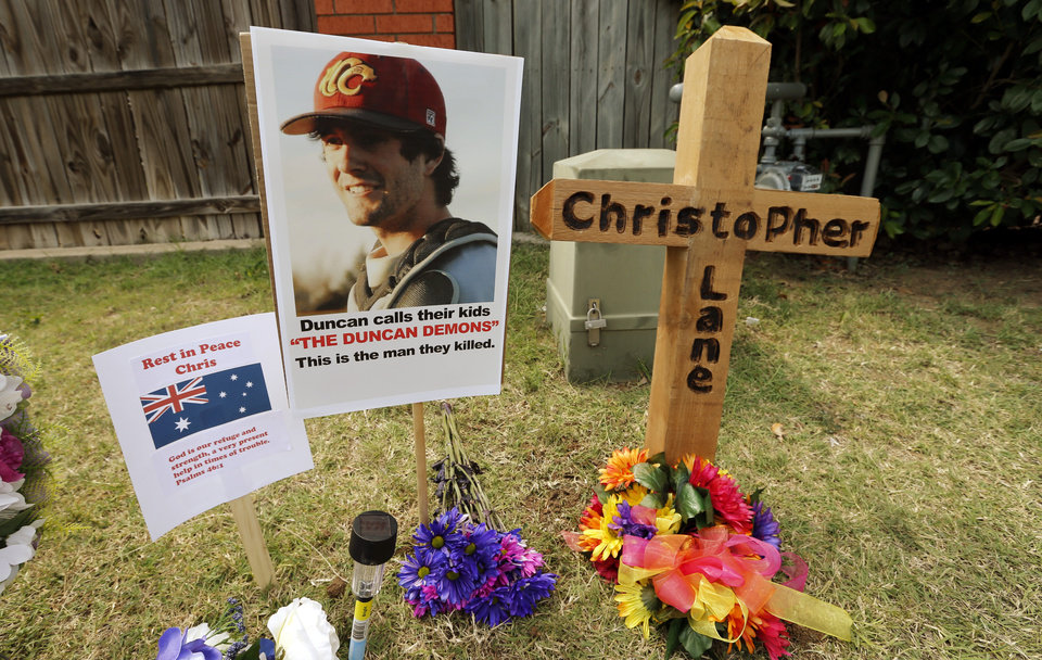 Photo - CHRISTOPHER LANE MURDER: A memorial to Christopher Lane has developed on Country Club Road on Tuesday, Aug. 20, 2013 in Duncan, Okla.  Flowers posters and a cross mark the scene where he was shot and killid.   Photo by Steve Sisney, The Oklahoman