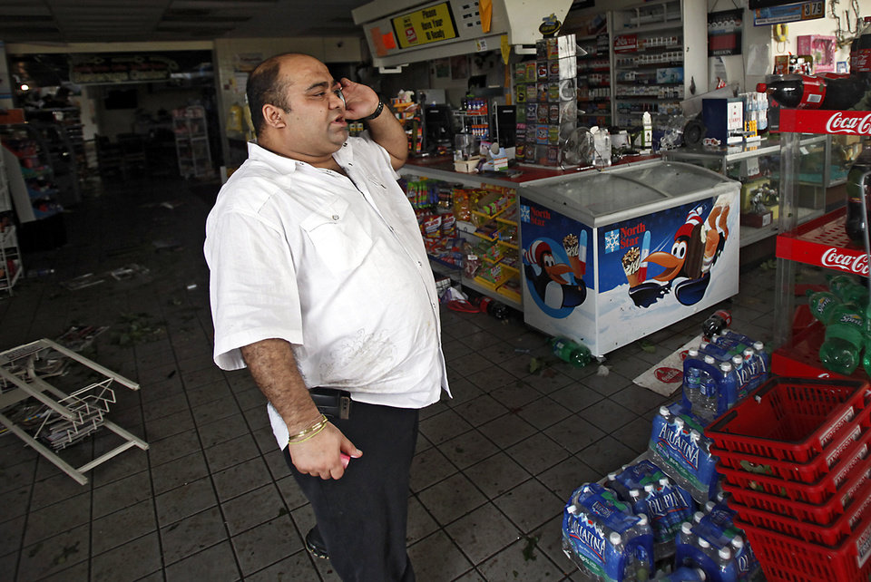 Photo - Anderson Travel Plaza owner Jay Kumar talks on the phone about the damage caused to his store after a tornado damaged the area around I-40 and Choctaw Road on Monday, May 10, 2010, in Oklahoma City, Okla.  Photo by Chris Landsberger, The Oklahoman
