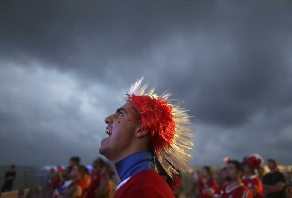 Photo - A soccer fan wearing a Mohawk-styled wig in Chile's team colors, cheers as he watches a live broadcast of the group B World Cup match between Chile and Spain, inside the FIFA Fan Fest area on Copacabana beach, in Rio de Janeiro, Brazil, Wednesday, June 18, 2014. Chile defeated Spain, the defending champs, 2-0. (AP Photo/Leo Correa)