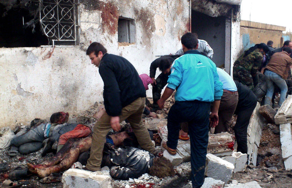 EDS NOTE: GRAPHIC CONTENT - This image taken from the Edlib News Network, ENN, which has been authenticated based on its contents and other AP reporting, shows Syrians removing the bodies of those killed after a government airstrike hit the Hama Suburb of Halfaya, Syria, Sunday, Dec. 23, 2012. A government airstrike on a rebel-held town in central Syria killed tens of people on Sunday, activists said, while the international envoy charged with negotiating an end to the country's civil war was in Damascus to meet with top officials. (AP Photo/Edlib News Network ENN)
