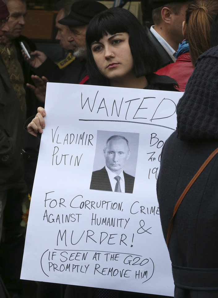 Photo - A woman holds an anti-Putin sign during a protest rally against the downing of Malayasia Airlines Flight MH17 in Sydney, Australia, Saturday, July 19, 2014. Australian Prime Minister Tony Abbott on Saturday called for an independent, international investigation into the downing of a Malaysian jetliner in Ukraine and demanded Russia's full cooperation. (AP Photo/Rob Griffith)