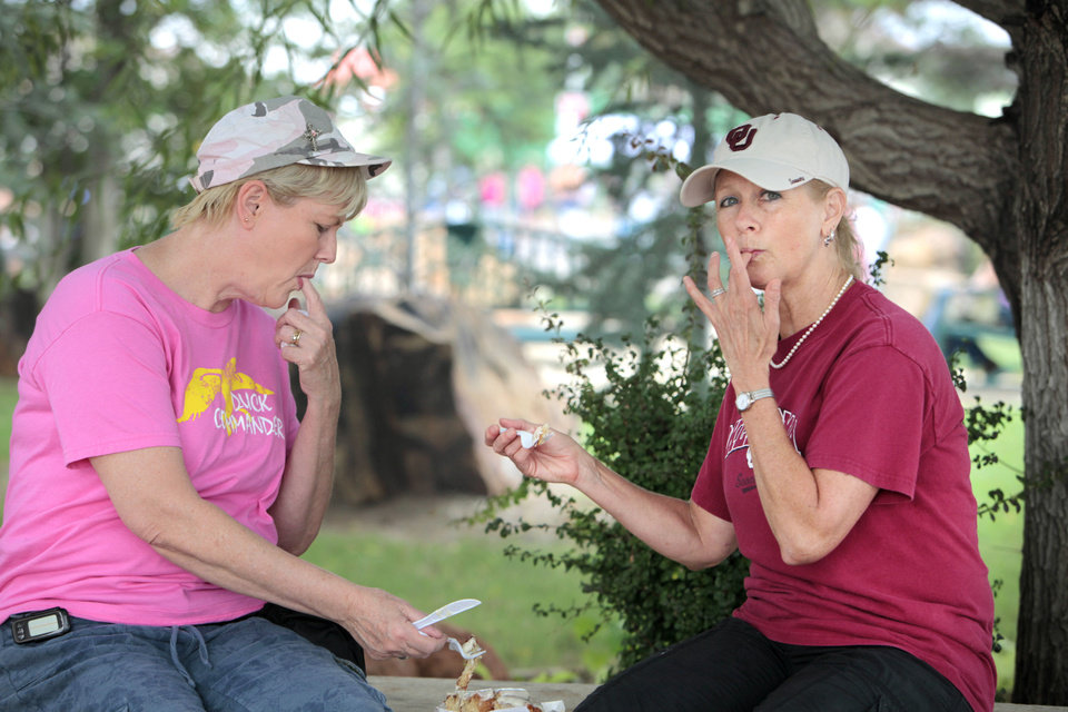 Photo - Finger licking good. T.C. Cunningham, OKC, and her sister Joni Roe, Choctaw, share a cinnamon roll at the Oklahoma State Fair , Friday, September 13, 2013.  Photo by David McDaniel, The Oklahoman  David McDaniel - The Oklahoman