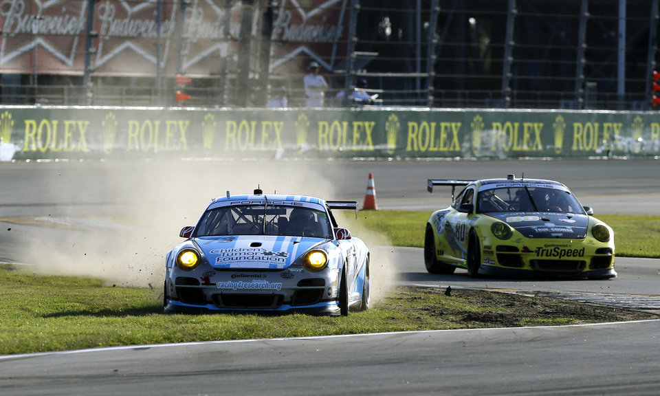 Photo - Patrick Long, left, in a Porsche GT3, slides off the track in front of Kelly Collins, in a Porsche GTS (80), during the Grand-Am Series Rolex 24 hour auto race at Daytona International Speedway, Saturday, Jan. 26, 2013, in Daytona Beach, Fla. (AP Photo/John Raoux)