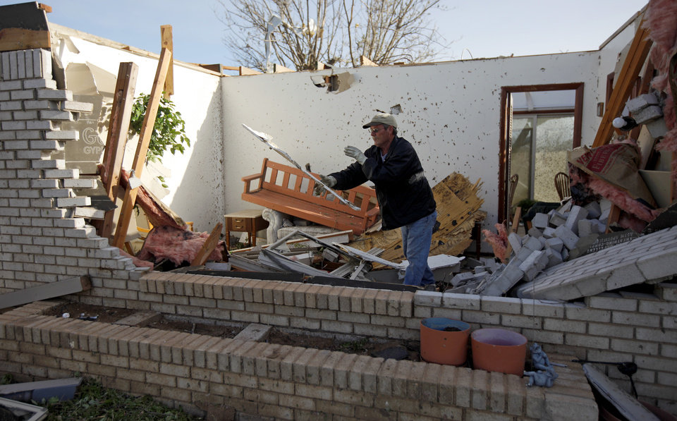 Photo - Norman Nelson clears out debris at his mother's home in Woodward, Okla., Sunday, April 15, 2012. A tornado that killed five people struck Woodward, Okla., shortly after midnight on Sunday, April15, 2012. Photo by Bryan Terry, The Oklahoman
