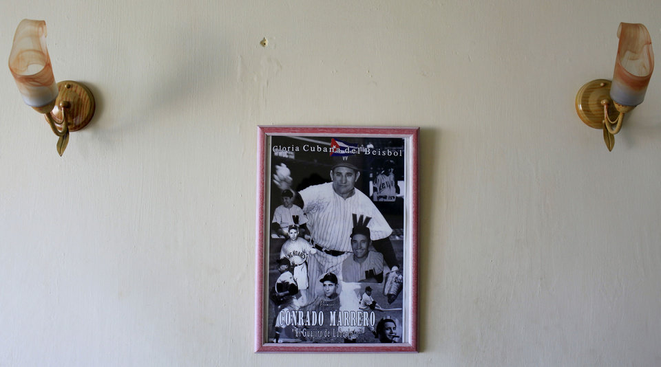 Photo - In this April 23, 2013 photo, pictures of Cuba's former pitcher Conrado Marrero hangs on the wall of his home in Havana, Cuba.  Marrero, the world's oldest living former major league baseball player, turns 102 on Thursday, April 25.  In addition to his longevity, the former Washington Senator has much to celebrate this year. After a long wait, he finally received a $20,000 payout from Major League baseball granted to old-timers who played between 1947 and 1979. The money had been held up since 2011 due to issues surrounding the 51-year-old U.S. embargo on Cuba, which prohibits most bank transfers to the Communist-run island. But the payout finally arrived in two parts, one at the end of last year, and the second a few months ago, according to Marrero's family. (AP Photo/Franklin Reyes)
