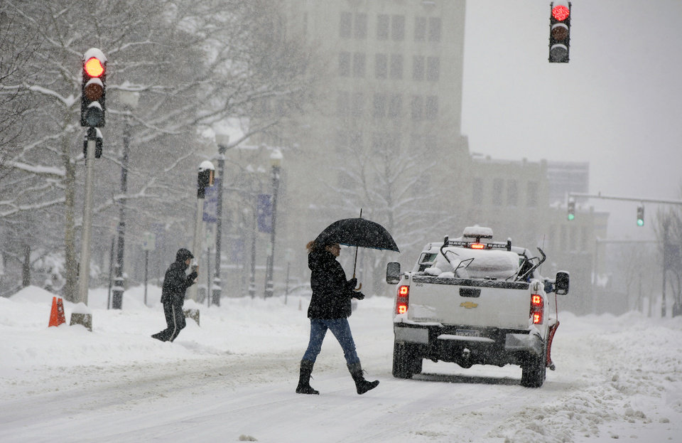 Photo - Pedestrians cross Orbit Way at the intersection of Ladge Drive during a snowstorm in Quincy, Mass., Wednesday, Feb. 5, 2014. The storm is expected to drop a foot or more of snow on some areas of Massachusetts Wednesday making driving treacherous. (AP Photo/Stephan Savoia)