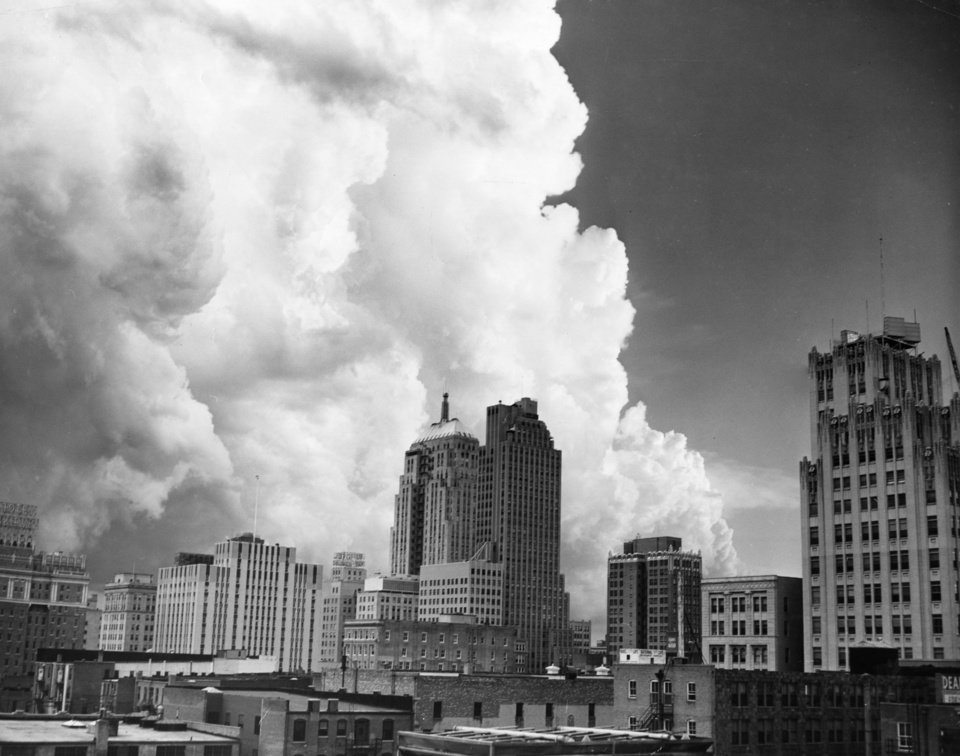 OKLAHOMA CITY / SKY LINE / OKLAHOMA:  SPOOKY OVERHEAD - This is the big cloud that tried to dump a tornado on the south end of Oklahoma City Thursday night.  A photographer caught this interesting shot across the Oklahoma City skyline shortly before 7 p.m. About the same time residents lined downtown streets as if expecting a parade.  But they were looking up as small funnels swirled down from the cloud base but failed to come to earth.  The threatening cloud with the dark base and fleecy top gave Midwest City a brief hailstorm and induced and electrical display over most of the city.  Staff Photographer Bill Burns.  Photo dated 05/22/1952 and unpublished.  Photo arrived in library on 05/23/1952.