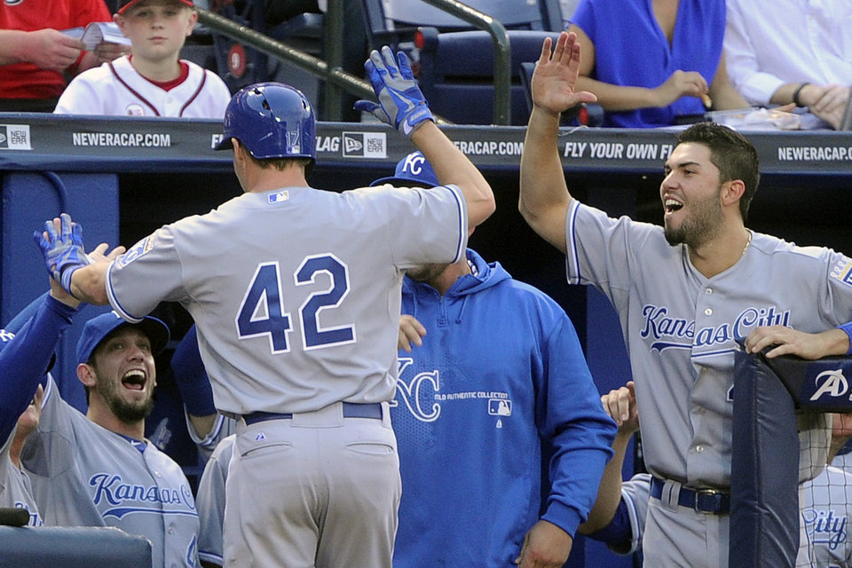 Kansas City Royals' Chris Getz, wearing 42 in honor of Jackie Robinson, is congratulated as he enters the dugout after a home run against the Atlanta Braves during the third inning of a baseball game, Tuesday, April 16, 2013, in Atlanta. (AP Photo/John Amis)
