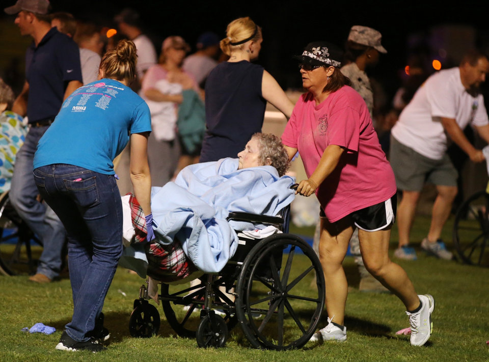 Photo - An elderly person is assisted at a staging area at a local school stadium  following an explosion at a fertilizer plant Wednesday, April 17, 2013, in West, Texas. An explosion at a fertilizer plant near Waco caused numerous injuries and sent flames shooting high into the night sky on Wednesday. (AP Photo/ Waco Tribune Herald, Rod Aydelotte)