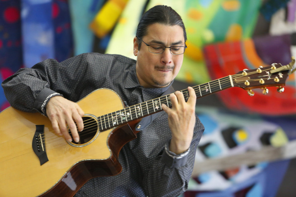 Photo - Acoustic Guitarist Edgar Cruz preforms in the Lobby of the Oklahoma Tower during a Art Moves concert in Oklahoma City, Friday February 07, 2014. Art Moves moves is sponsored by Devon Energy and provides free arts events in downtown area each work day from Noon-1:00. Photo By Steve Gooch, The Oklahoman  Steve Gooch - The Oklahoman
