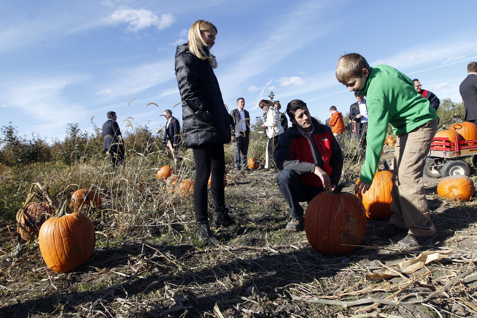 Photo -   Republican vice presidential candidate, Rep. Paul Ryan, cneter, R-Wis., and his wife Janna help their son Charlie pick a pumpkin at the Apple Holler farm pumpkin patch, Sunday, Oct. 7, 2012 in Sturtevant, Wis. (AP Photo/Mary Altaffer)