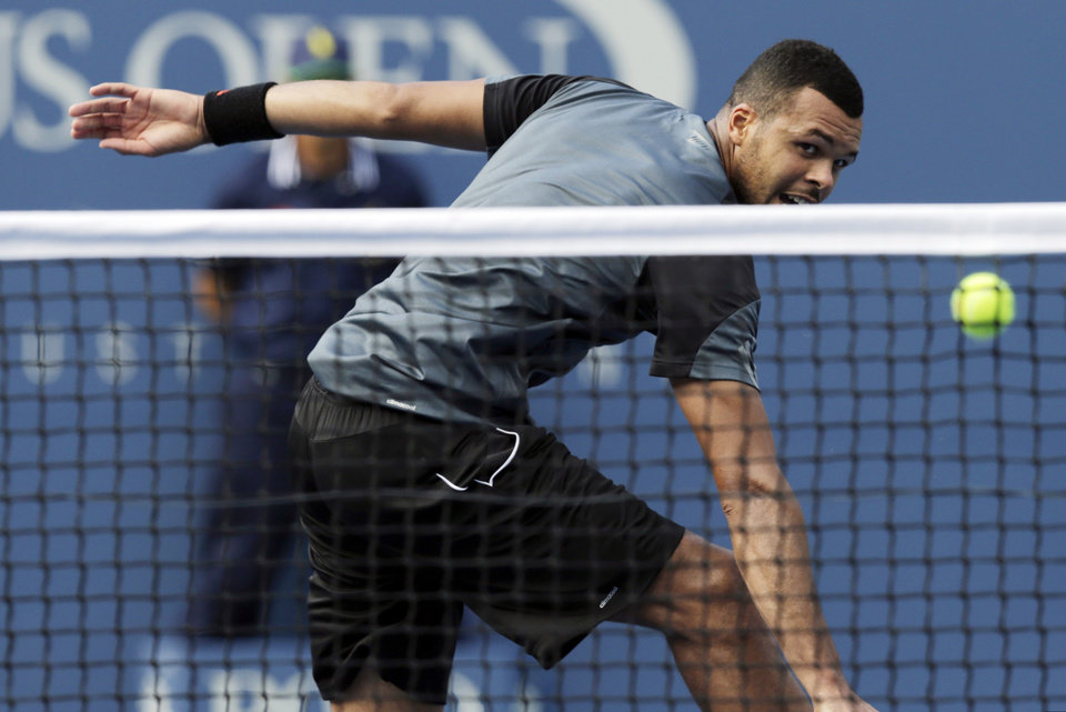 Photo - Jo-Wilfried Tsonga, of France, returns a shot against Andy Murray, of the United Kingdom, during the fourth round of the 2014 U.S. Open tennis tournament, Monday, Sept. 1, 2014, in New York. (AP Photo/Charles Krupa)
