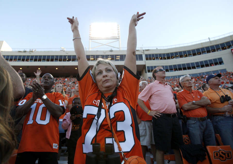 Photo - Cindy Story, mother of Oklahoma State offensive lineman Levy Adcock, celebrates a Cowboy touchdown during OSU's game vs. Arizona on Thursday in Stillwater. PHOTO BY SARAH PHIPPS, The Oklahoman