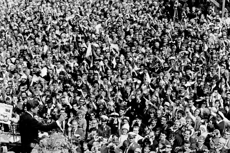 FILE - In this June 26, 1963 file photo, U.S. President John F. Kennedy, left, waves to a crowd of more than 300,000 gathered to hear his speech where he declared
