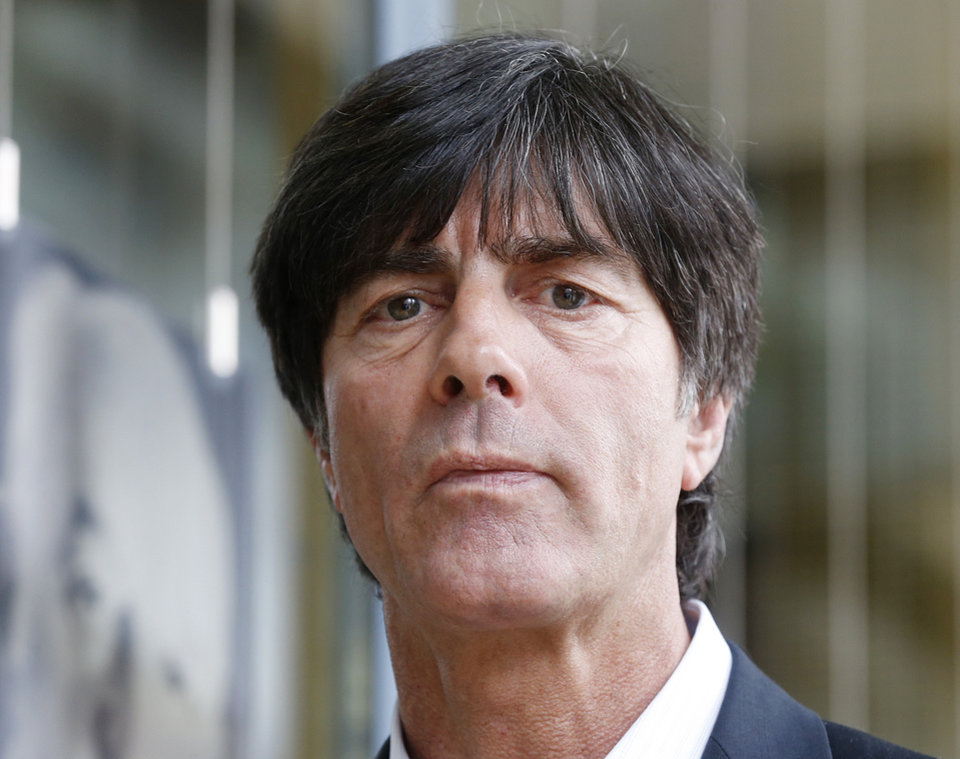 Photo - Coach of the German national soccer team Joachim Loew is on his way to a press conference where he will present his preliminary team for the upcoming World Cup in Brazil in Frankfurt, Germany, Thursday, May 8, 2014. (AP Photo/Michael Probst)