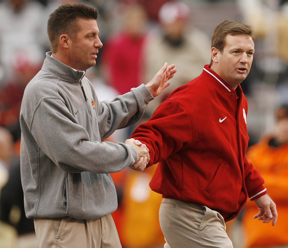 Photo - Oklahoma State coach Mike Gundy and Oklahoma coach Bob Stoops, from left, shake hands before the college football game between the University of Oklahoma Sooners (OU) and the Oklahoma State University Cowboys (OSU) at the Gaylord Family-Memorial Stadium on Saturday, Nov. 24, 2007, in Norman, Okla.  Photo By Bryan Terry, The Oklahoman