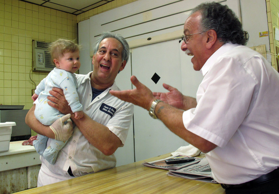 Photo - John Sacco Sr. hands his 6-month-old grandson, Jack Russo, to Pete Canu, a customer in Sacco's Elizabeth, N.J., butcher shop, Thursday, June 20, 2013. Canu says he liked the realism and human flaws of actor James Gandolfini's Tony Soprano character, but Sacco said,