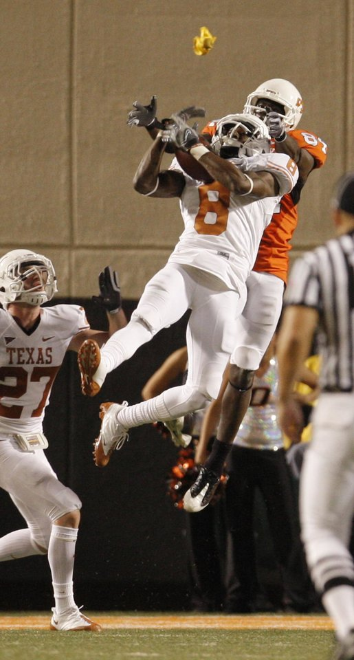 Photo - A flag flies through the air as Texas Chykie Brown (8) intercepts a pass intended for Hubert Anyiam (84) during the college football game between the Oklahoma State University Cowboys (OSU) and the University of Texas Longhorns (UT) at Boone Pickens Stadium in Stillwater, Okla., Saturday, Oct. 31, 2009. Photo by Doug Hoke, The Oklahoman