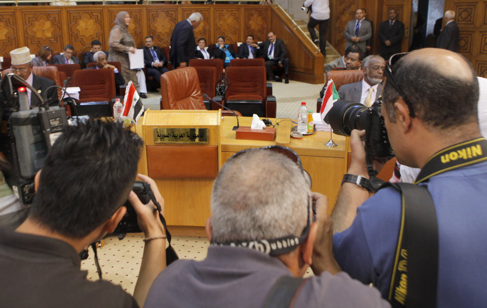 Photo -   Cameramen document the Syrian delegation's empty chairs during the Arab League's ministerial council meeting at the Arab League headquarters in Cairo, Egypt, Wednesday, Sept. 5, 2012. Egyptian President Mohammed Morsi said during the meeting that Syrian leader Bashar Assad must learn from 'recent history' and step down before it is too late. (AP Photo/Amr Nabil)