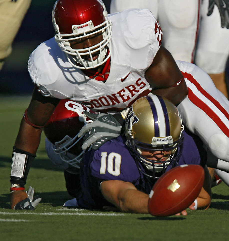 Photo - Oklahoma's Keenan Clayton (22) brings down Washington quarterback Jake Locker (10) as he fumbles the ball during the first half of the college football game between the University of Oklahoma Sooners (OU) and the University of Washington Huskies (UW) at Husky Stadium on Saturday, Sep. 13, 2008, in Seattle, Wash.   by Chris Landsberger, The Oklahoman ORG XMIT: KOD