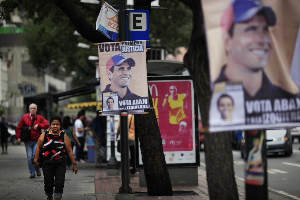 Election campaign posters promoting opposition presidential candidate Henrique Capriles hang on street polls in Caracas, Venezuela, Friday, Oct. 5, 2012. Venezuelans will head to the polls Sunday to vote in their country's presidential election, deciding on whether to keep President Hugo Chavez or seek change with opposition candidate Henrique Capriles. (AP Photo/Ariana Cubillos)