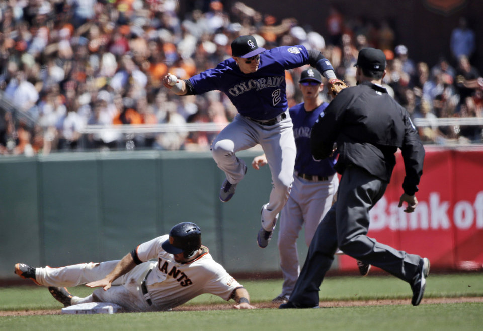 Photo - Colorado Rockies shortstop Troy Tulowitzki, top, leaps over San Francisco Giants' Brandon Hicks as he forces him out at second base on a ground ball from San Francisco Giants' Angel Pagan during the third inning of a baseball game on Sunday, April 13, 2014, in San Francisco. (AP Photo/Marcio Jose Sanchez)