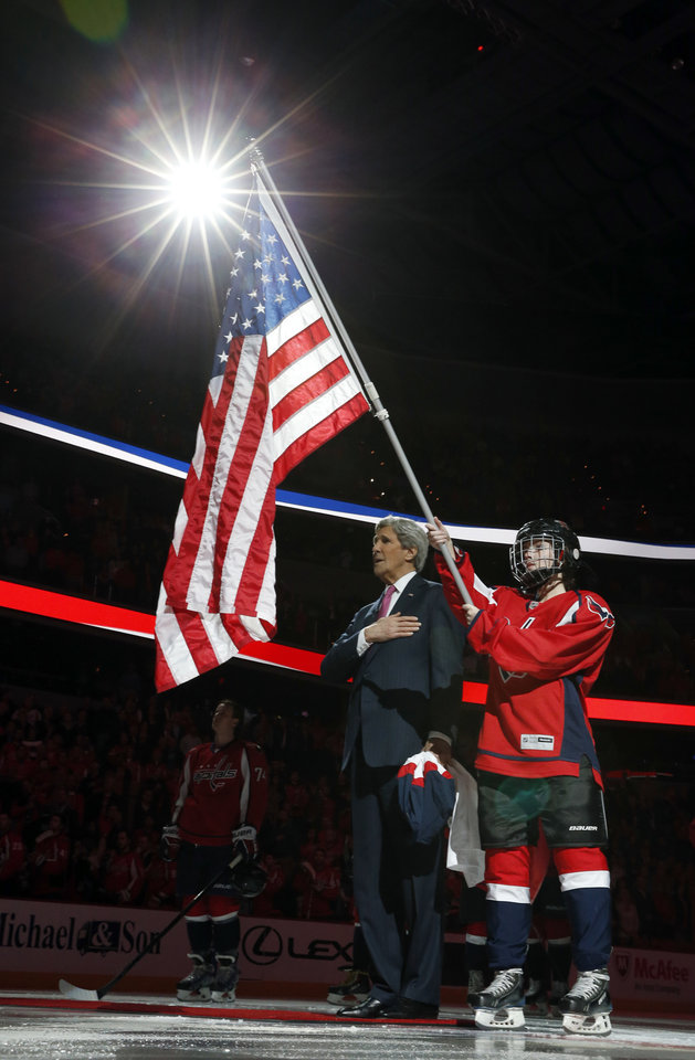 Photo - Secretary of State John Kerry stands during the National Anthem after participating in a ceremonial puck drop to honor those members of the Washington Capitals and Winnipeg Jets that have selected for their country's Olympic hockey team, Thursday, Feb. 6, 2014, in Washington. (AP Photo/Alex Brandon, Pool)