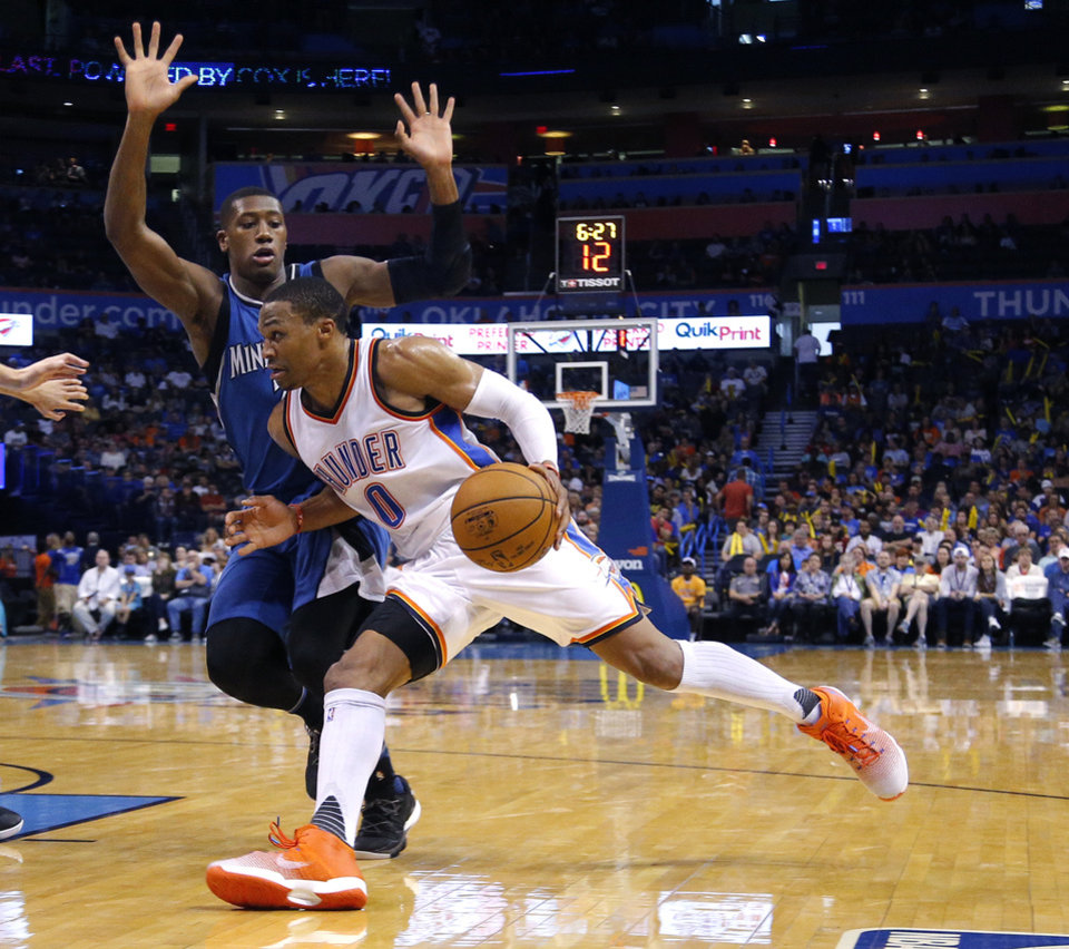 Photo - Oklahoma City's Russell Westbrook (0) drives to the basket as Minnesota's Kris Dunn (3) defends  during the NBA game between the Oklahoma City Thunder and the Minnesota Timberwolves at the Chesapeake Energy Arena, Sunday, Oct. 16, 2016.   Photo by Sarah Phipps, The Oklahoman