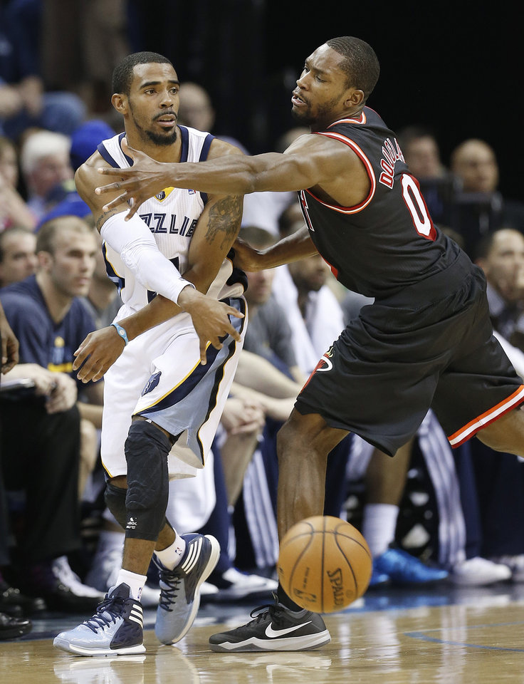 Photo - Memphis Grizzlies guard Mike Conley, left, passes around Miami Heat guard Toney Douglas (0) in the first half of an NBA basketball game Wednesday, April 9, 2014, in Memphis, Tenn. (AP Photo/Mark Humphrey)