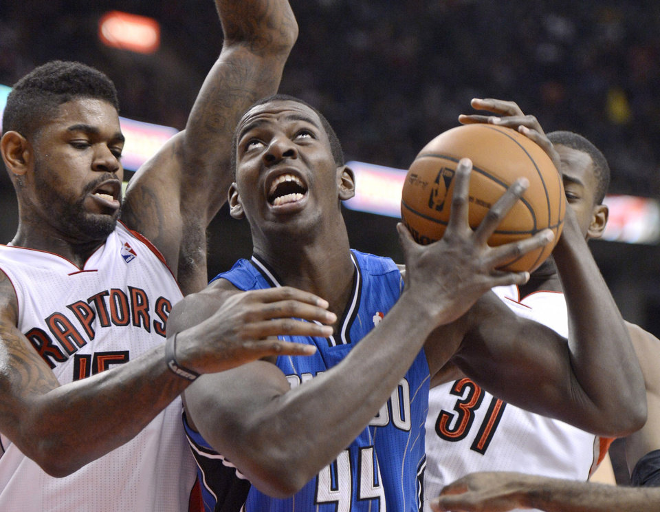 Photo - Orlando Magic forward Andrew Nicholson, 44, drives for the net as Toronto Raptors' Amir Johnson defends during first half NBA action in Toronto Friday, Dec. 21, 2012. (AP Photo/The Canadian Press, Frank Gunn)
