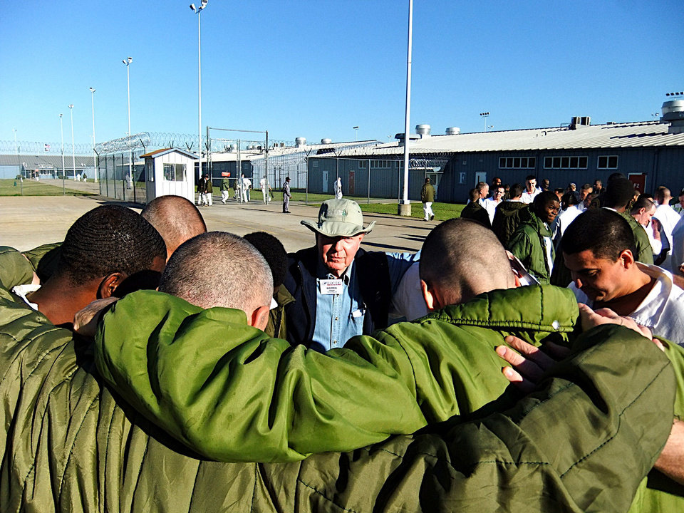 A church volunteer, center, prays with a group of inmates in a prison yard as part of a Bill Glass Weekend of Champions event. Photo provided