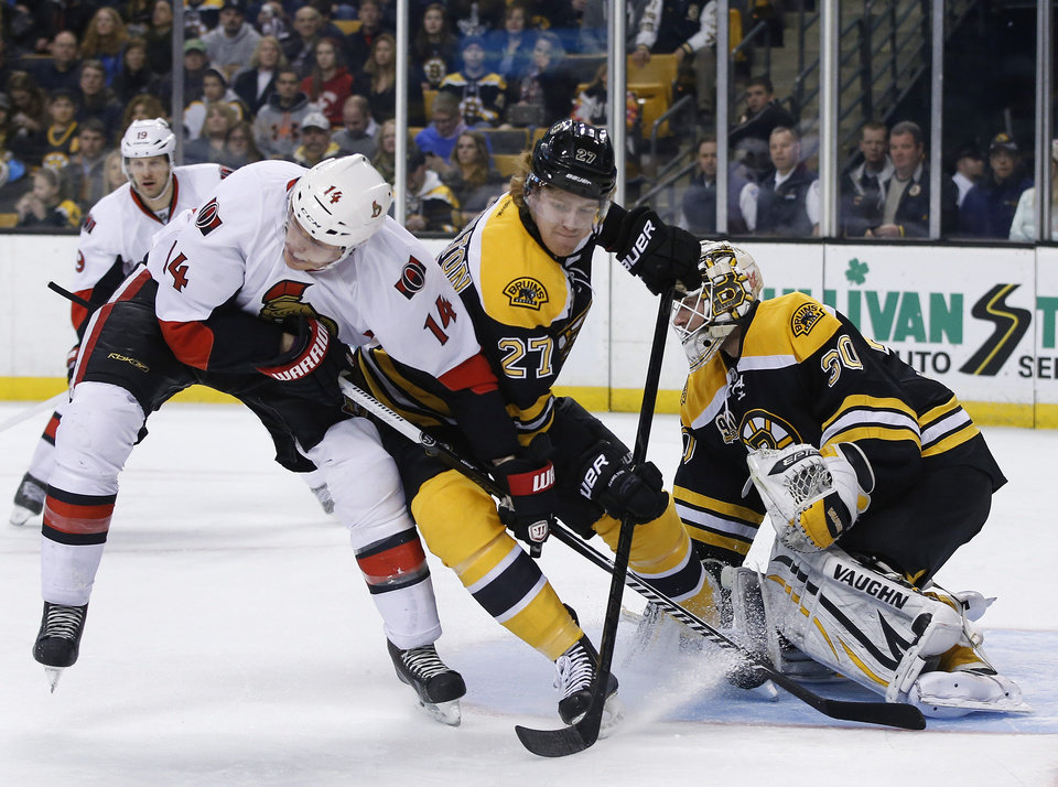 Photo - Boston Bruins defenseman Dougie Hamilton (27) keeps Ottawa Senators left wing Colin Greening (14) from getting position as Boston Bruins goalie Chad Johnson (30) protects the net during the first period of an NHL hockey game in Boston, Saturday, Feb. 8, 2014. (AP Photo/Elise Amendola)