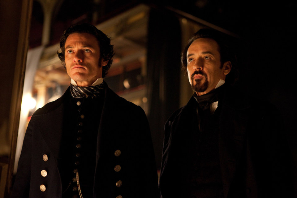 Photo - Luke Evans, left, portrays Detective Fields, and John Cusack portrays Edgar Allan Poe in a scene from the gothic thriller