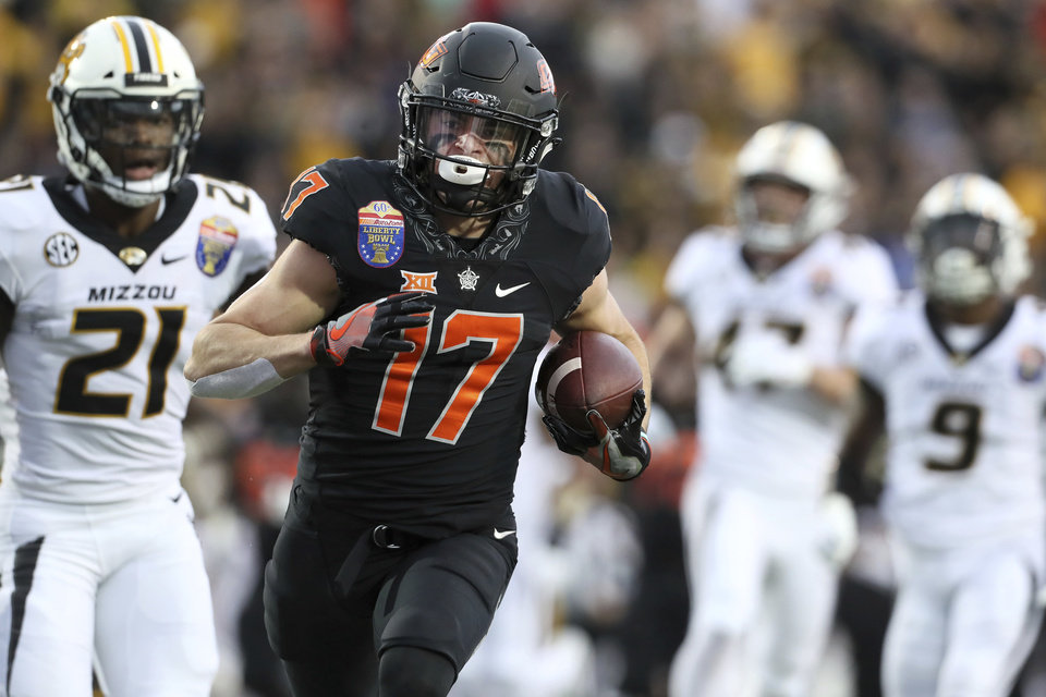Photo - Oklahoma State wide receiver Dillon Stoner (17) runs in for a touchdown in the first half against Missouri in the Liberty Bowl NCAA college football game in Memphis, Tenn., Monday, Dec. 31, 2018. (Joe Rondone/The Commercial Appeal via AP)