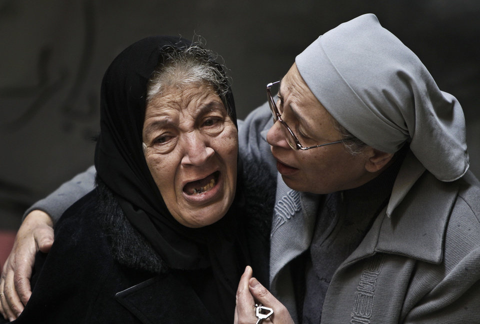 Photo -   FILE - In this Sunday, Jan. 2, 2011 file photo, an Egyptian Coptic Christian woman, left, is comforted by a Coptic nun, right, as she cries out in emotion following morning mass inside the Saints Church after 21 worshippers were killed in an apparent suicide bombing in Alexandria, Egypt. Despite his rhetoric and promises to uphold the civil nature of Egypt, Shafiq seemed to some Egyptians an odd choice for Christians who suffered attacks under Mubarak's near 30 year-rule, culminating in the bombing of a church in Alexandria that killed 21 people attending a New Year's Even Mass more than a year ago. (AP Photo/Ben Curtis, File)