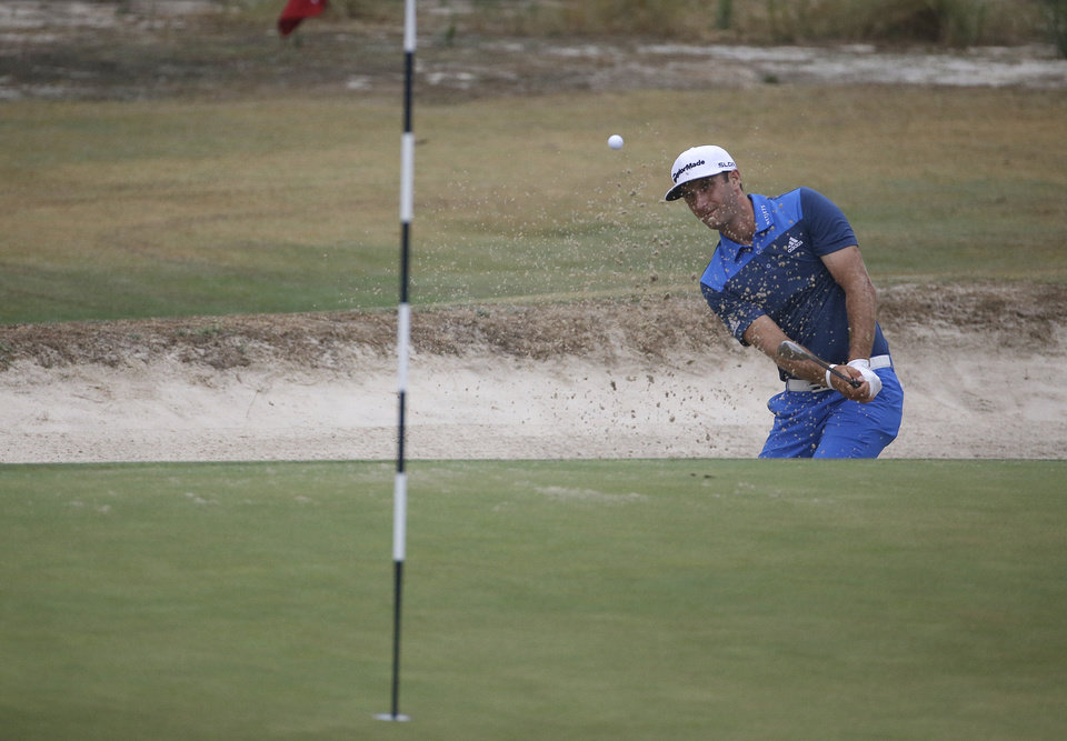 Photo - Dustin Johnson hit out of the bunker on the 12th hole during the second round of the U.S. Open golf tournament in Pinehurst, N.C., Friday, June 13, 2014. (AP Photo/David Goldman)